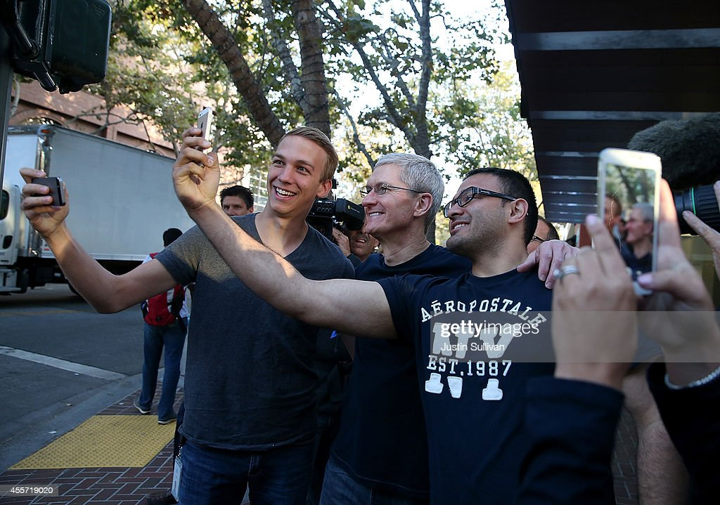 Apple CEO Tim Cook takes a selfie photo with a people waiting in line to buy the new iPhone 6 at an Apple Store on September 19 2014 in Palo Alto...