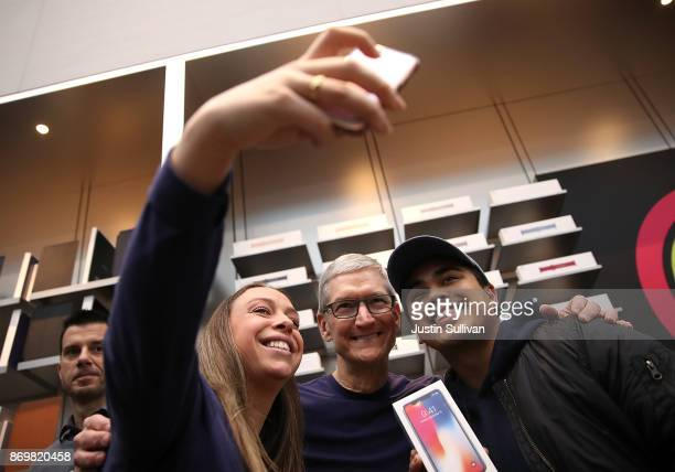 Apple CEO Tim Cook takes a selfie with customers as the new iPhone X goes on sale at an Apple Store on November 3 2017 in Palo Alto California The...