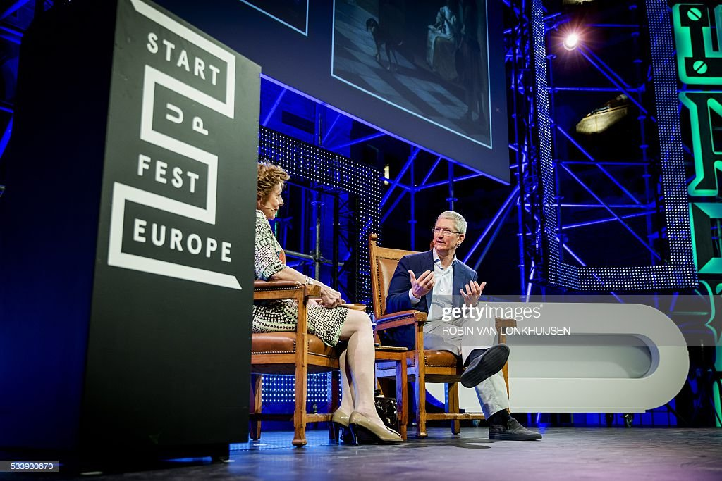 Apple CEO Tim Cook (R) talks with Dutch businesswoman, former polician and European commissioner, Neelie Kroes (L), during the StartupDelta at the Startup Fest Europe in Amsterdam on May 24, 2016. The Startup Fest Europe gathers international keynote-speakers to discuss the latest innovations, products and services. The event runs from May 24 to 28, 2016. / AFP / ANP / Robin van Lonkhuijsen / Netherlands OUT