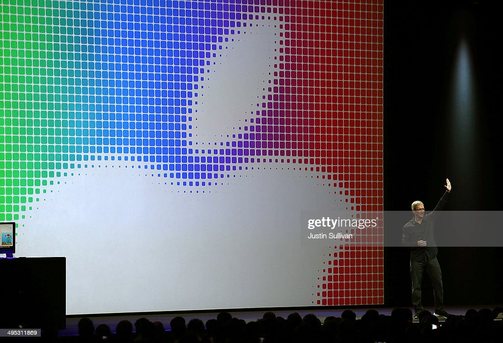Apple CEO Tim Cook waves during the Apple Worldwide Developers Conference at the Moscone West center on June 2 2014 in San Francisco California Tim...