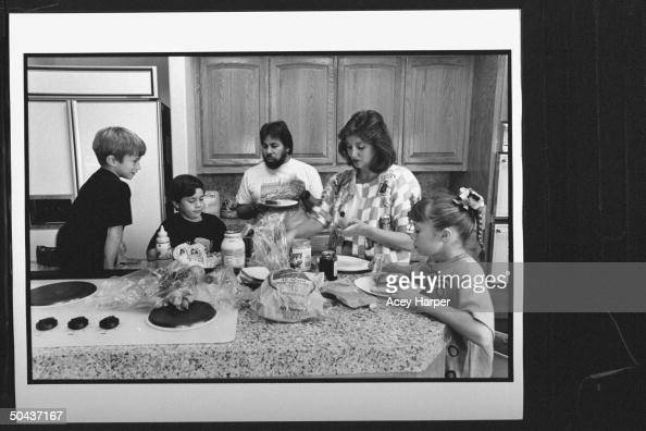 Apple Computer cofounder Steve Wozniak w his lawyer wife Suzanne Mulkern gathered around kitchen counter w his kids Gary Jesse Sarah busy making...