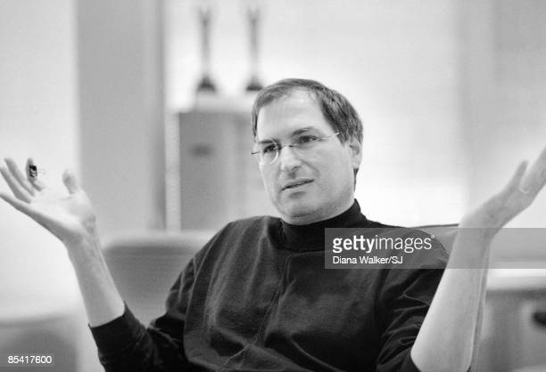 Apple Computer head Steve Jobs deep in thought propping sneakered feet on conference table in boardroom at Apple HQ day before heading to Boston for...