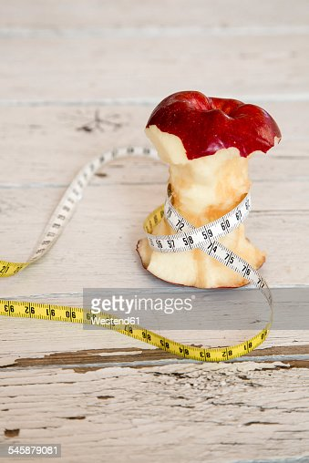Apple core and tape measure on wood