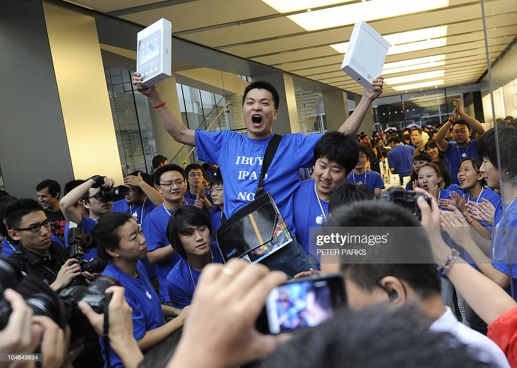 Apple customer Han Ziwen shouts holding his ipads outside Apple's flagship store in Beijing after queuing for 60 hours to be one of the first to officially buy an iPad in China on September 17, 2010. Apple officially launches its iPad in China -- a solid business move, analysts say, even though Chinese customers have been able to buy the tablet computer on the grey market for months. AFP PHOTO/Peter PARKS
