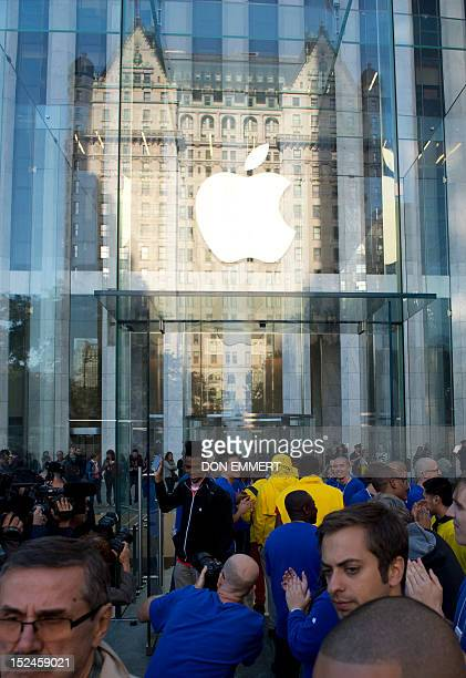 Apple employees applaud as shoppers enter and exit the Apple store on Fifth Avenue as the new iPhone 5 is delivered on September 21 2012 in New York...
