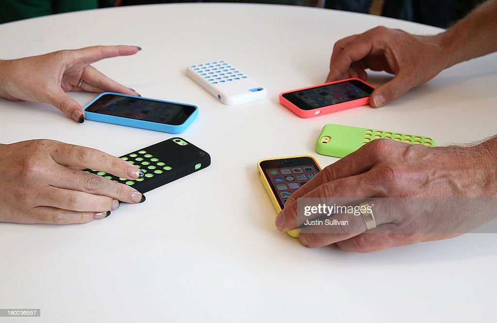 Apple employees arrange a display of the new iPhone 5C during an Apple product announcement at the Apple campus on September 10, 2013 in Cupertino, California. The company launched the new iPhone 5C model that will run iOS 7 is made from hard-coated polycarbonate and comes in various colors and the iPhone 5S that features fingerprint recognition security.