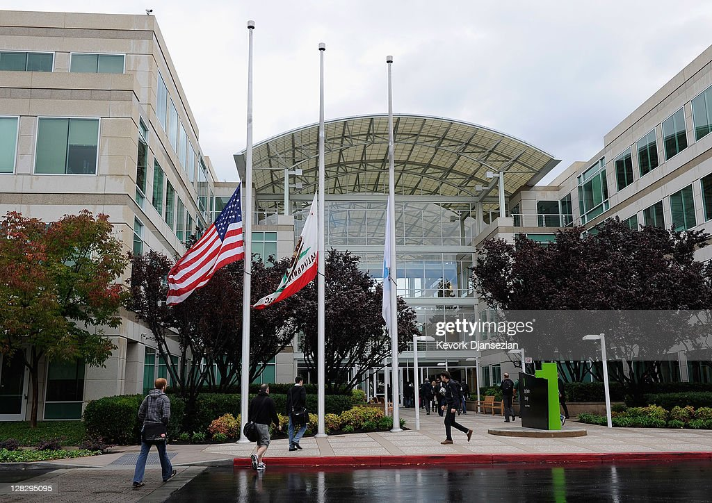 Apple employees arrive to work as they pass flags flying at half staff following the death of Steve Jobs at the Apple headquarters on October 5 2011...
