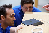 Apple employees compare the thickness of an iPhone and a new 'iPad mini' on the morning of the tablet's launch in the Apple Store in Covent Garden on...