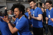 Apple employees rally with Apple enthusiasts who were waiting in line to enter the new Apple Store on Kurfuerstendamm avenue on its opening day on...