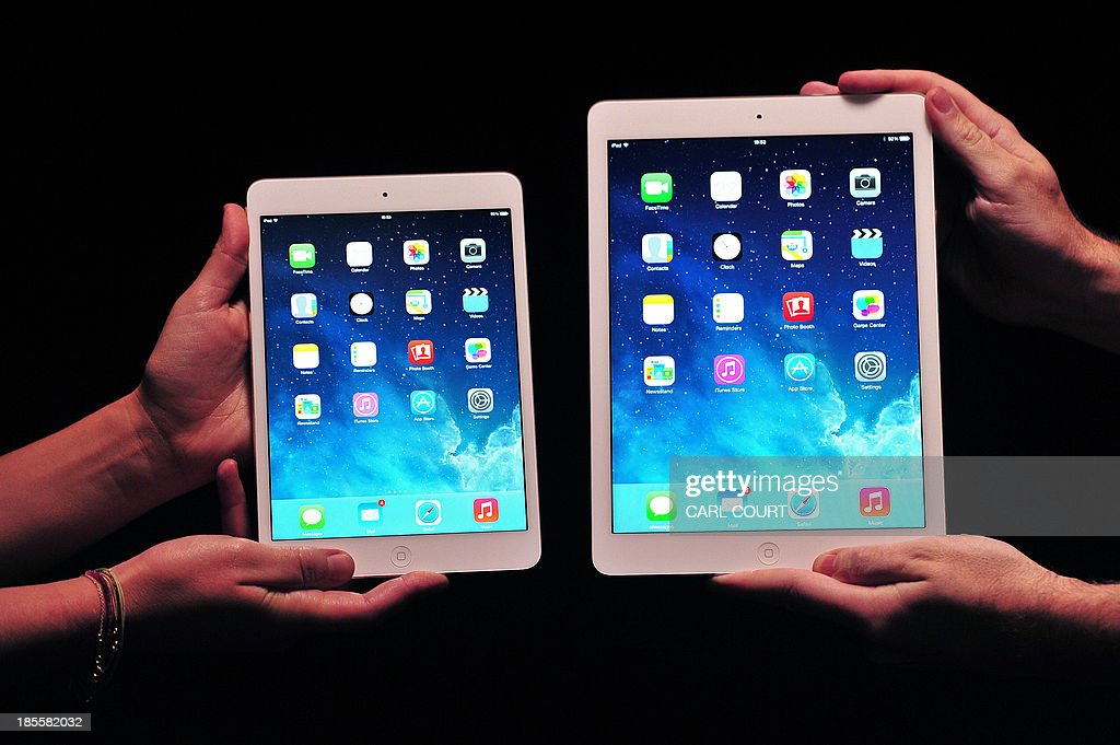 Apple employees show off the new iPad Air (R) and iPad Mini at a satellite launch event in central London on October 22, 2013. AFP PHOTO/CARL COURT