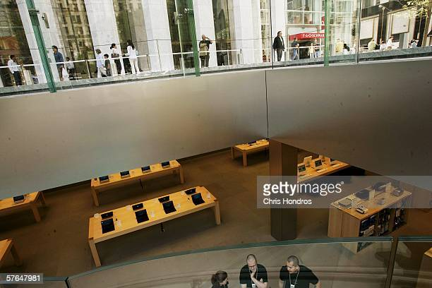 Apple employees stand on the store floor under a glass cube that encloses the entrance to an underground Apple Store on Fifth Avenue May 18 2006 in...