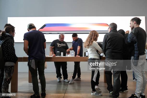 Apple employees talk with customers about the new iPhone 8 at the Fifth Avenue Apple Store September 22 2017 in New York City The new iPhone 8 and...