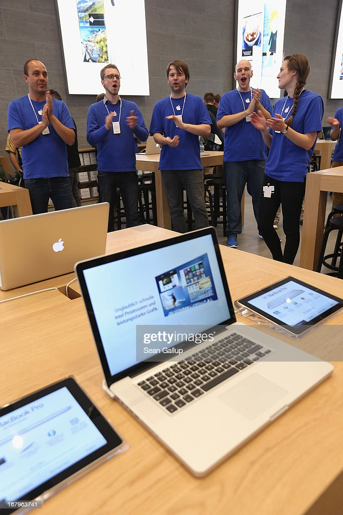 Apple employees welcome visitors as they enter the new Apple Store on Kurfuerstendamm avenue on its opening day on May 3, 2013 in Berlin, Germany. Thousands of people waited to enter the store, which is Apple's first in Berlin and its biggest in Germany.
