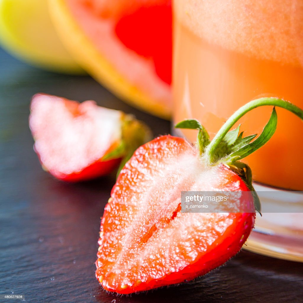 Apple, grapefruit and strawberry smoothie and ingredients, dark stone background : Stock Photo