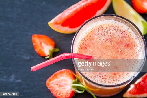 Apple, grapefruit and strawberry smoothie and ingredients, dark stone background : Stockfoto
