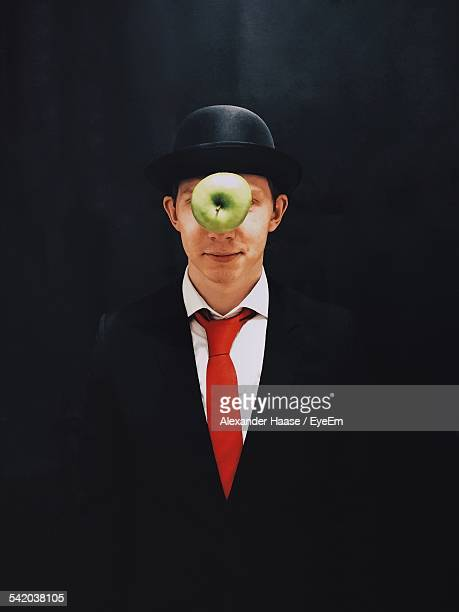 Apple In Mid-Air In Front Of Man With Hat Against Black Background
