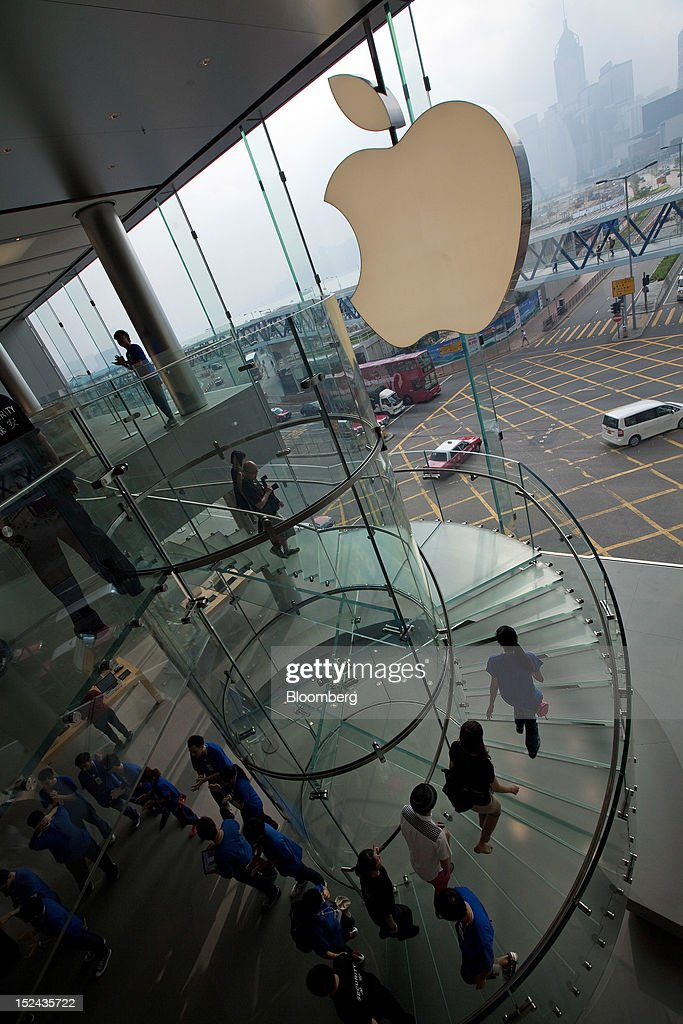 Apple Inc. employees and customers ascend a staircase at the company's store in Hong Kong, China, on Friday, Sept. 21, 2012. Apple Inc. is poised for a record iPhone 5 debut and may not be able to keep up with demand as customers line up from Sydney to New York to pick up the latest model of its top-selling product. The device hits stores in eight countries today at 8 a.m. local time, giving customers in Australia the first chance to buy the device. Photographer: Daniel J. Groshong/Bloomberg via Getty Images