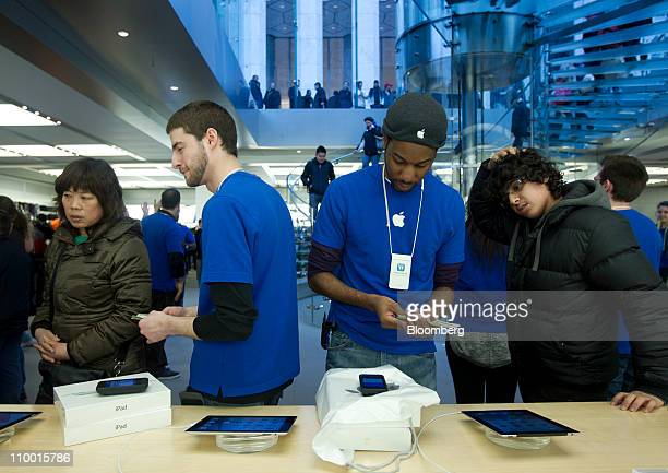 Apple Inc employees check out customers purchasing the iPad 2 at the Apple flagship retail store in New York US on Friday March 11 2011 Apple Inc may...