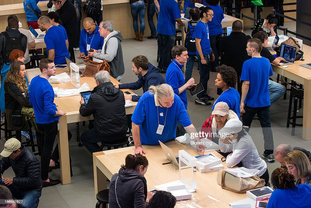 Apple Inc. employees help shoppers on the first day of sales of the new iPad Air at the 5th Avenue Apple store in New York, U.S., on Friday, Nov. 1, 2013. Apple Inc.'s forecast for the slowest holiday sales growth in a half decade reflects how iPhones and iPads aren't providing the growth surges they once did as competition accelerates in the saturated mobile market. Photographer: Craig Warga/Bloomberg via Getty Images