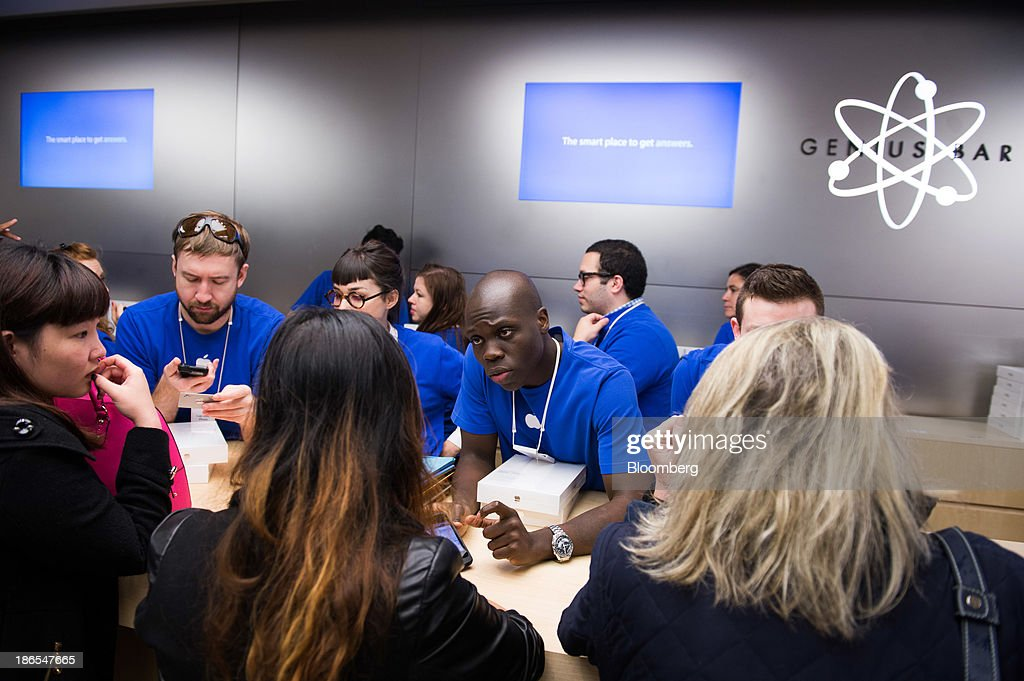 Apple Inc. employees help shoppers purchase the new iPad Air on the first day of sales at the 5th Avenue Apple store in New York, U.S., on Friday, Nov. 1, 2013. Apple Inc.'s forecast for the slowest holiday sales growth in a half decade reflects how iPhones and iPads aren't providing the growth surges they once did as competition accelerates in the saturated mobile market. Photographer: Craig Warga/Bloomberg via Getty Images