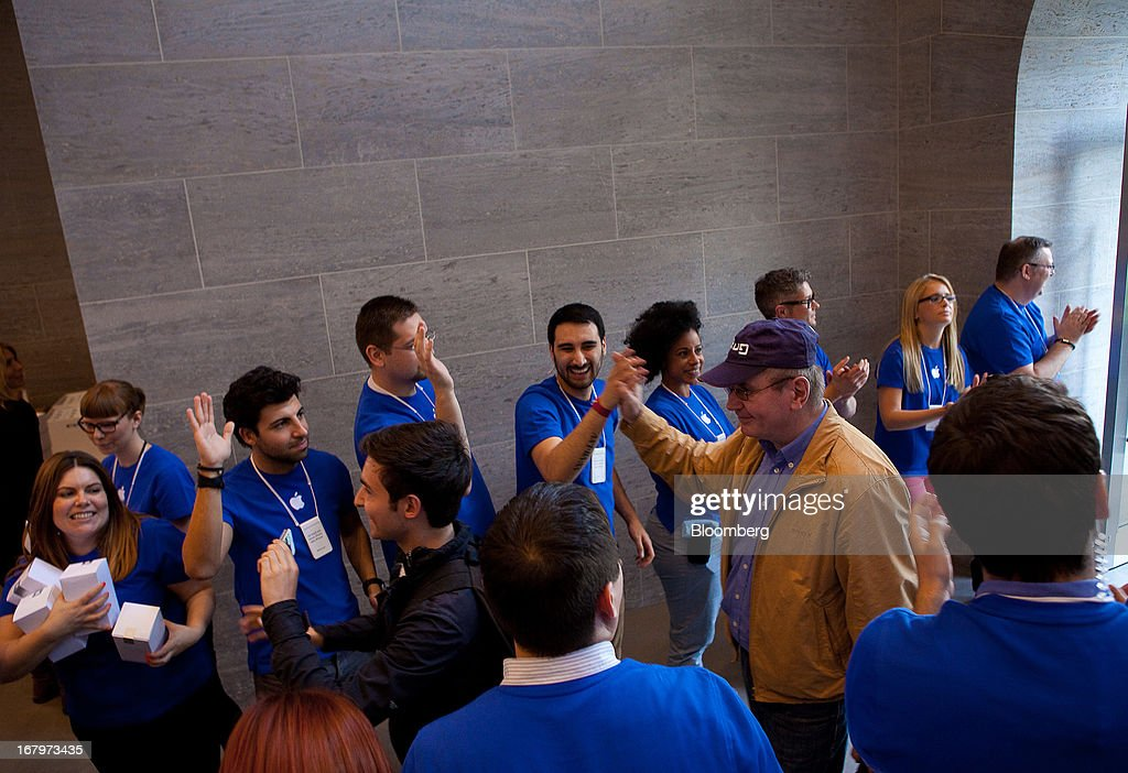 Apple Inc. employees stand and applaud as a customer enters the new Apple Inc. store located on Kurfurstendamm Street in Berlin, Germany, on Friday, May 3, 2013. Apple Inc.'s latest showcase store, their first in the German capital city will open its doors to the public today. Photographer: Krisztian Bocsi/Bloomberg via Getty Images