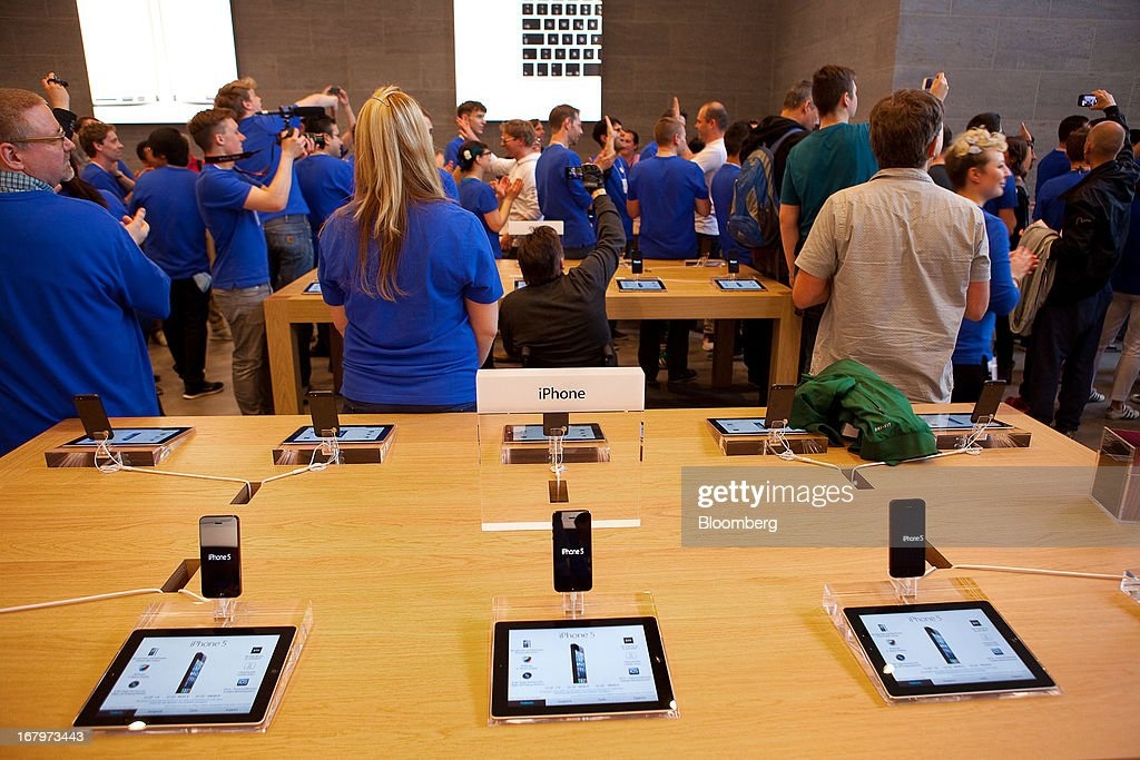 Apple Inc. employees stand and applaud as a customers enter the new Apple Inc. store located on Kurfurstendamm Street in Berlin, Germany, on Friday, May 3, 2013. Apple Inc.'s latest showcase store, their first in the German capital city will open its doors to the public today. Photographer: Krisztian Bocsi/Bloomberg via Getty Images