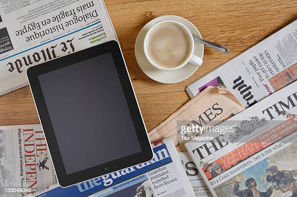 Apple iPad tablet computer on a wooden table with newspapers and a coffee session for Tap Magazine taken on February 8 2011