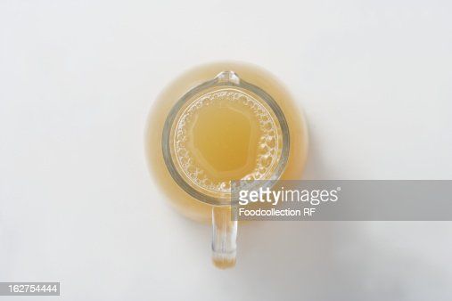 Apple juice in glass jug, overhead view