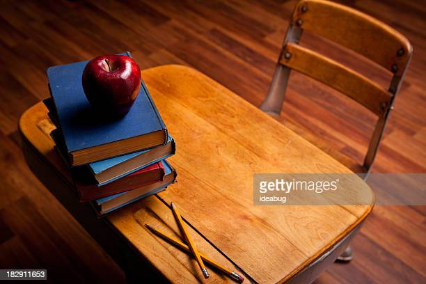 Apple, Pencils, Old Books on School Desk and Hardwood Floor