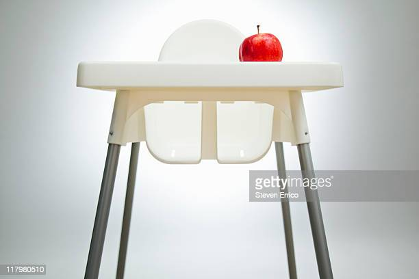 Apple sitting on a high chair