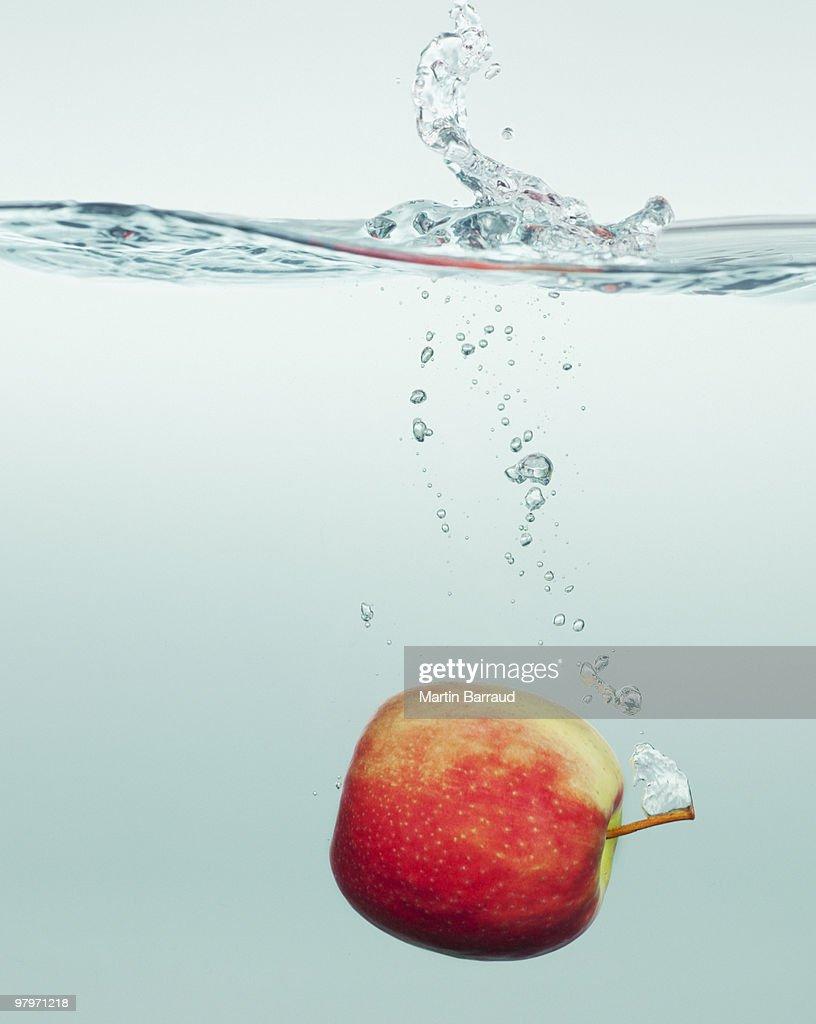Apple splashing in water : Stock Photo