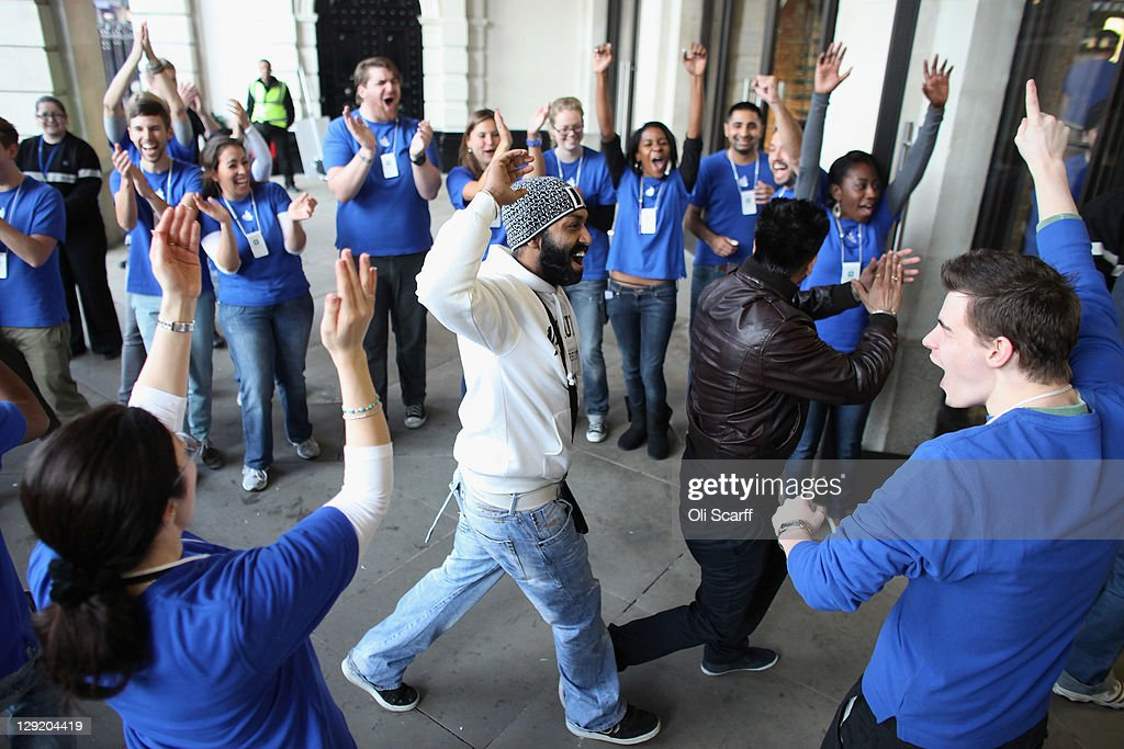 Apple staff applaud a customer as he enters the Apple store in Covent Garden to buy an iPhone 4S on October 14, 2011 in London, England. The widely anticipated new mobile phone from Apple has seen customers queue in cities around the world for hours to be amongst the first to buy the device.