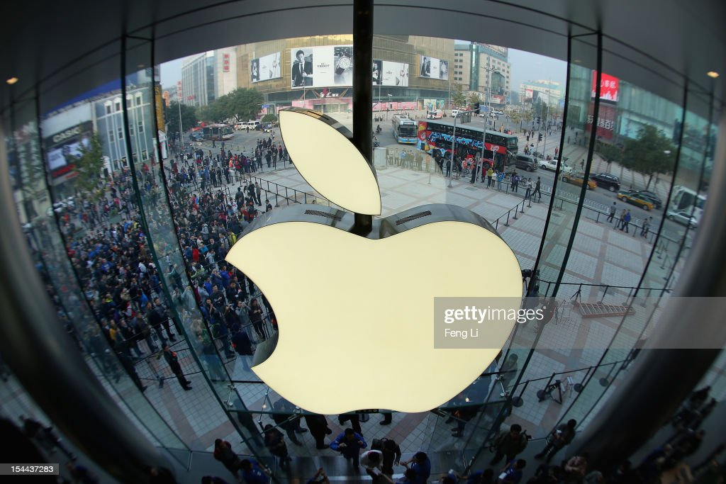 Apple staff members celebrate as customers coming the Wangfujing store on October 20, 2012 in Beijing, China. Apple Inc. opened its sixth retail store on the Chinese mainland Saturday. The new Wangfujing store is Apple's largest retail store in Asia.