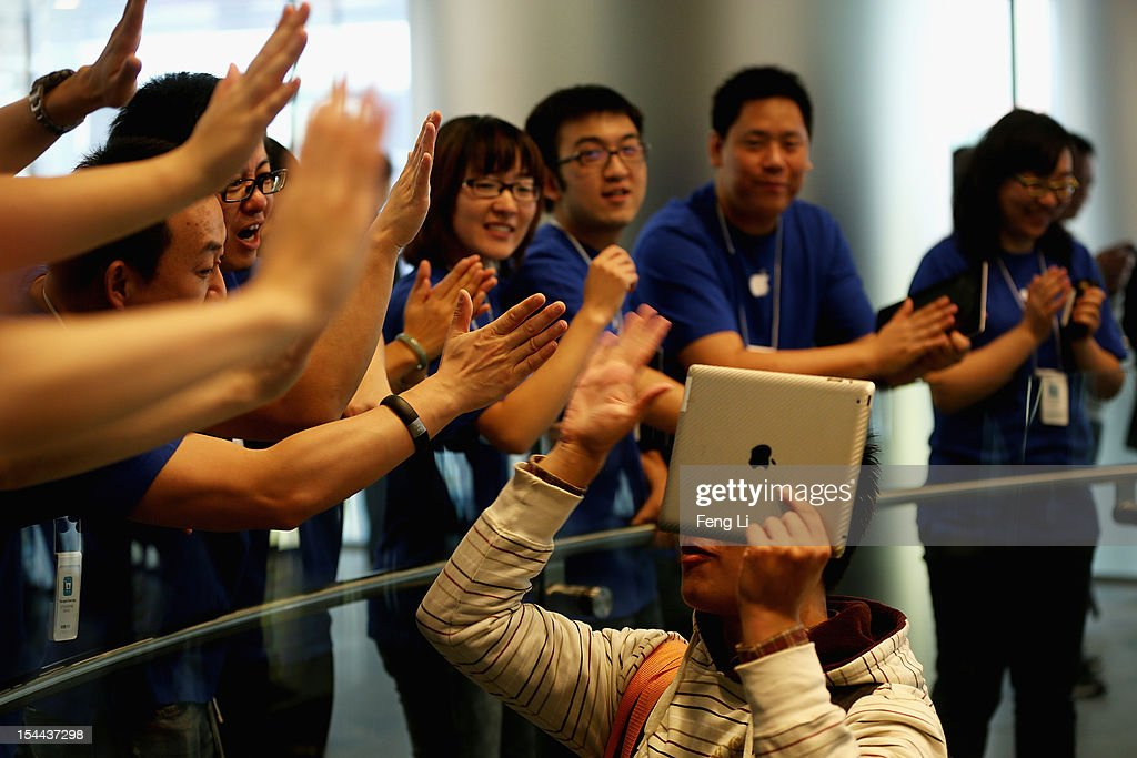 Apple staff members celebrate with a customer holding his iPad in the Wangfujing store on October 20, 2012 in Beijing, China. Apple Inc. opened its sixth retail store on the Chinese mainland Saturday. The new Wangfujing store is Apple's largest retail store in Asia.