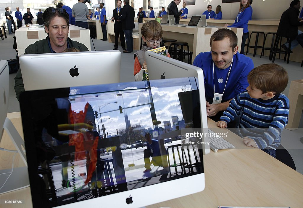 Apple Store employee Michael Louden (2R) works with Davin Roe (R), 3, as Apple employee Jason Roth (L) and his son Jake Roth, 6, play on an iMac at the Apple Store during a preview for the new store on October 21, 2010 in Chicago, Illinois. The new store opens on October 23 in Lincoln Park, a part of the city's Near North Side that has been trendy for several years.