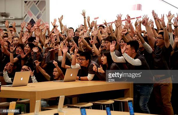 Apple store employees gather to celebrate the opening of a new store in Dalian China's Liaoning province on October 24 2015 US technology giant Apple...