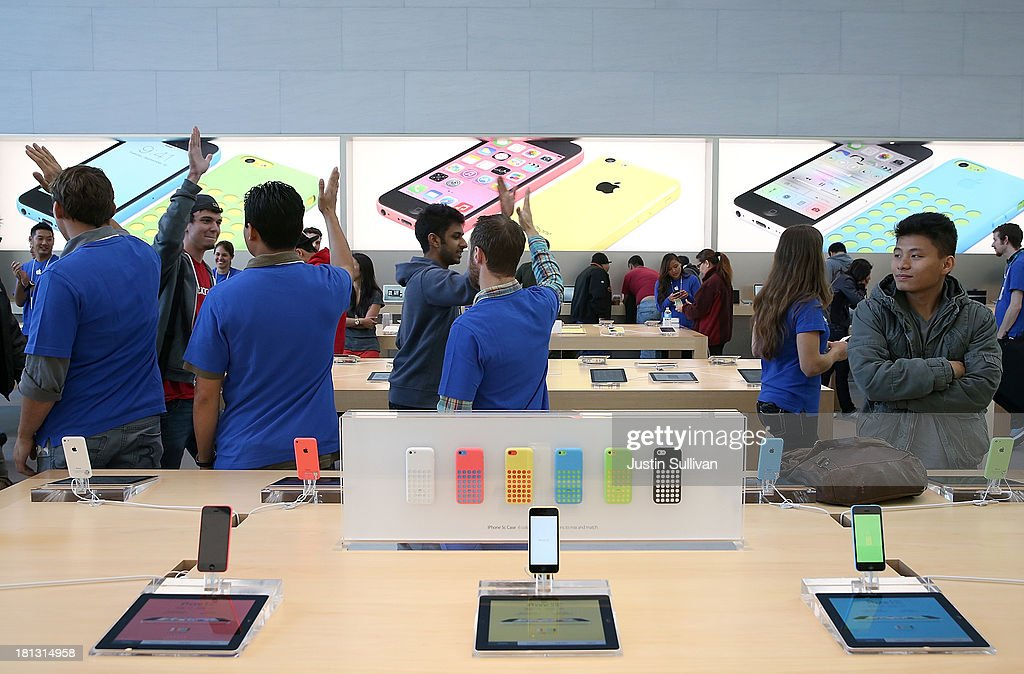 Apple Store employees greet customers who are purchasing the new iPhone on September 20, 2013 in Palo Alto, California. Apple launched two new models of iPhone: the iPhone 5S, which is preceded by the iPhone 5, and a cheaper, paired down version, the iPhone 5C. The phones come with a new operating system.