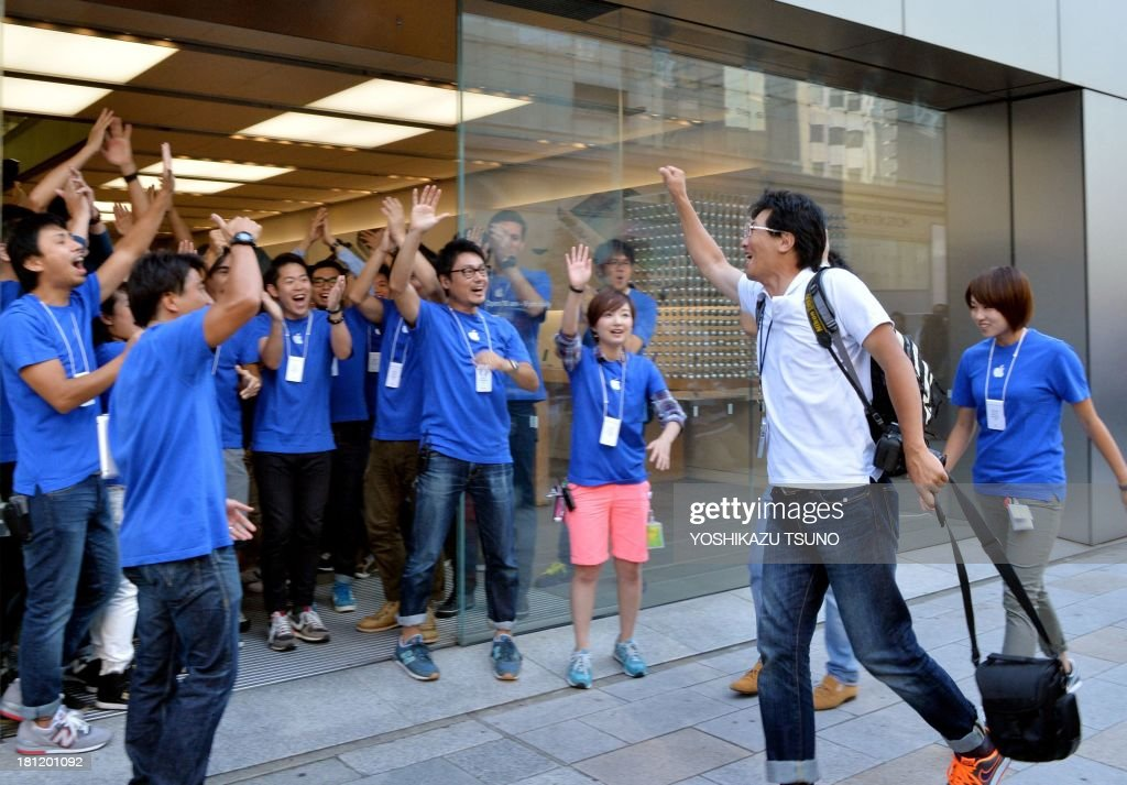 Apple Store employees greet their first customer (2nd R) for the day after 700 Apple fans queued to buy Apple's new iPhone 5s and 5c smartphones at the Apple Store in Tokyo on September 20, 2013. Apple acolytes got their hands on new iPhones in the global roll-out of two new models, but failure to make headway in China and complaints about the price struck a sour note. AFP PHOTO / Yoshikazu TSUNO