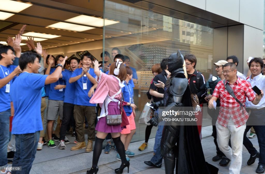 Apple Store employees greet their first customers after 700 Apple fans queued to buy Apple's new iPhone 5s and 5c smartphones at the Apple Store in Tokyo on September 20, 2013. Apple acolytes got their hands on new iPhones in the global roll-out of two new models, but failure to make headway in China and complaints about the price struck a sour note. AFP PHOTO / Yoshikazu TSUNO