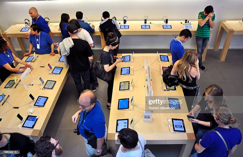 Apple Store employees help customers as they sample the various Apple mobile devices at an Apple Store in San Francisco California