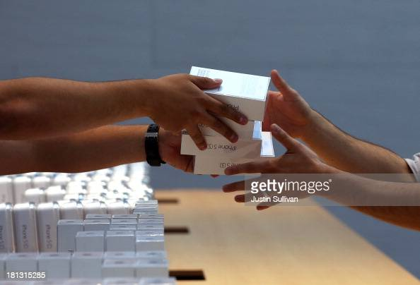 Apple Store employees pass boxes of the new Apple iPhone 5S on September 20 2013 in Palo Alto California Apple launched two new models of iPhone the...
