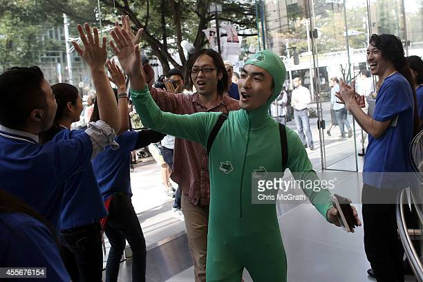 Apple store staff high five customers as they enter the store to purchase the new iPhones at the launch of the new Apple iPhone 6 and iPhone 6 plus...