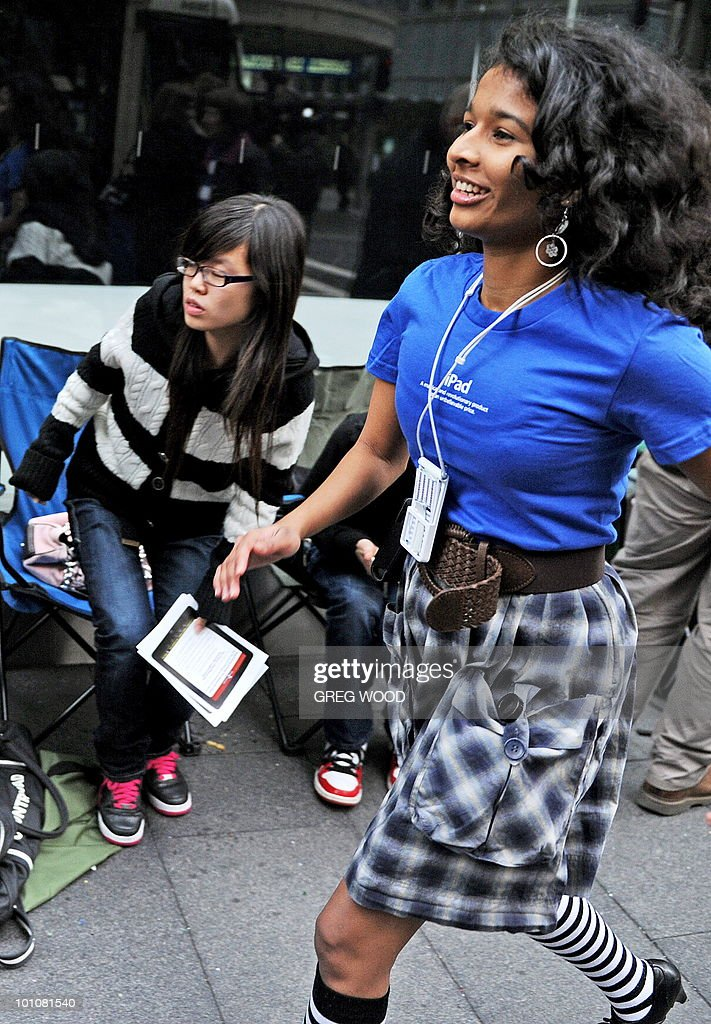 Apple store staff (blue) interact with members of the public lined up outside Apple's flagship store in Sydney on May 28, 2010 just prior to the much-hyped iPad going on sale. The iPad -- a buttonless tablet computer targeted at the leisure market -- is also going on sale in Japan, Britain, Canada, France, Germany, Italy, Japan, Spain and Switzerland on May 28 as part of a staggered global roll-out. AFP PHOTO / Greg WOOD