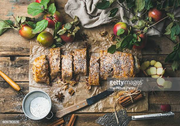 Apple strudel cake with cinnamon and sugar powder cut in slices served with star anise, nuts and fresh apples on rustic wooden background