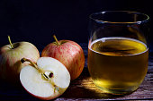 A glass cider with a few apples beside it