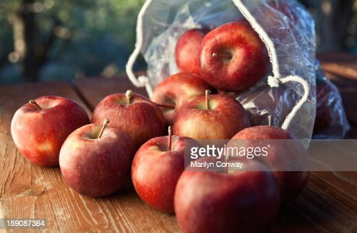 Apples and a sack on a wooden table outdoors : Stock Photo