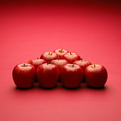 Apples arranged in triangle, red background
