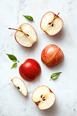 Apples flat lay on a marble background. Group of sliced and whole apple fruits viewed from above. Top view