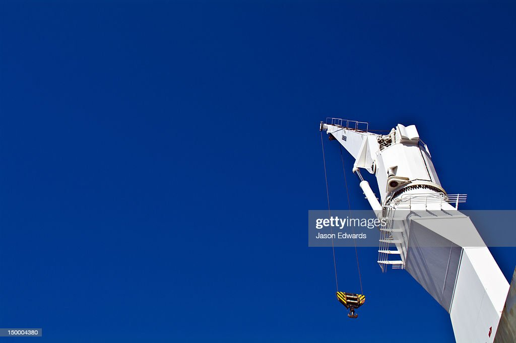 The boom and hook of a ships crane towers over the deck cargo hold.