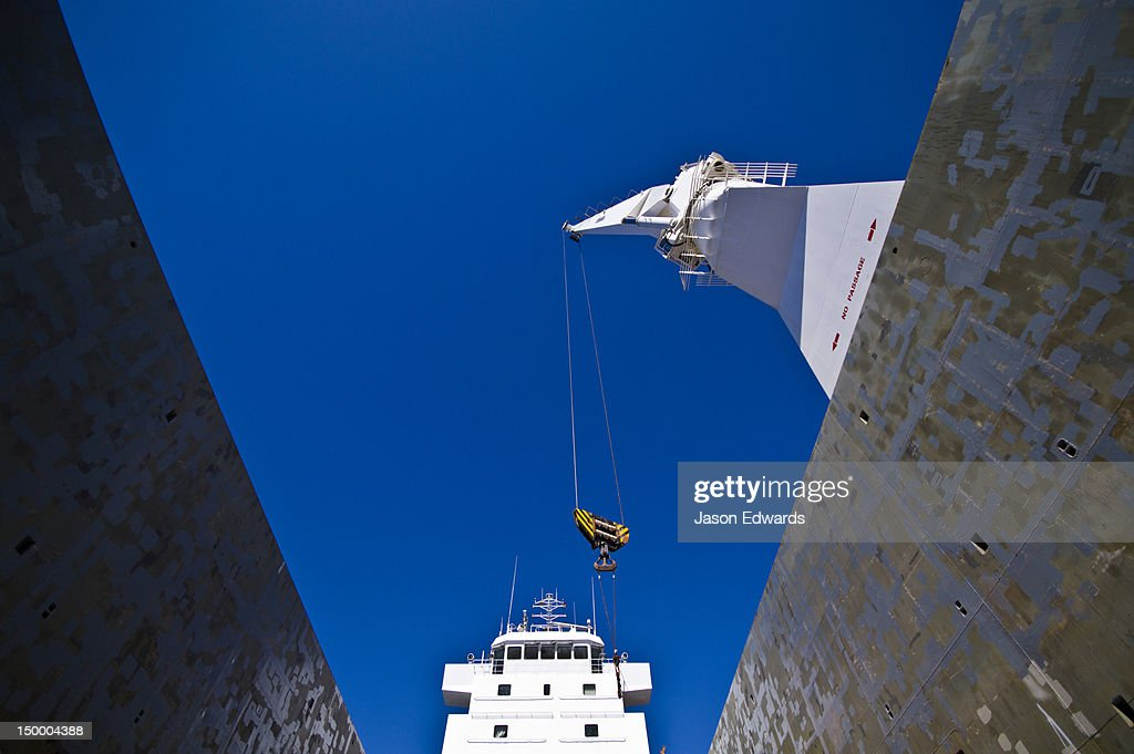 The boom and crane of a ships crane towers over the deck cargo hold.